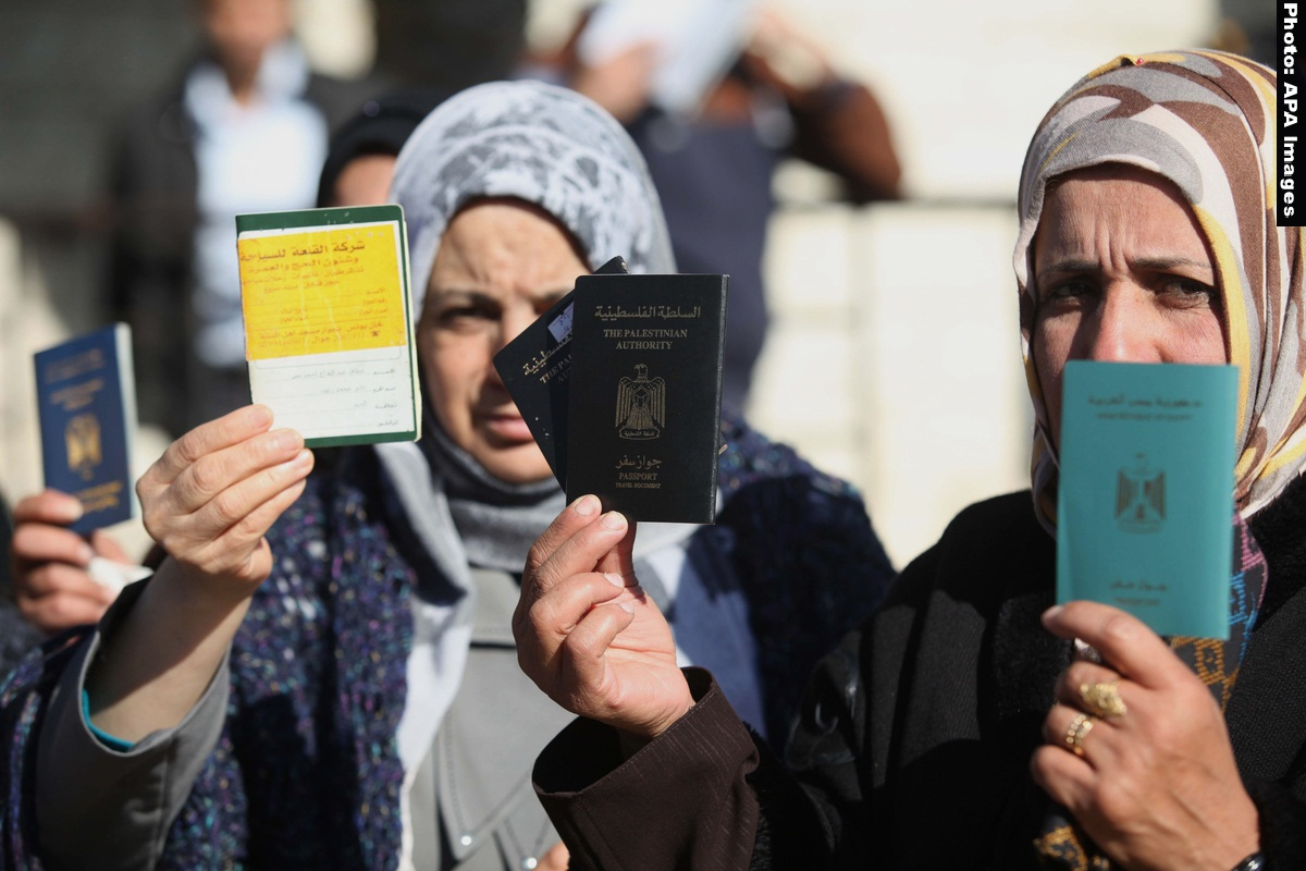 Palestinian women hold their passports during a protest