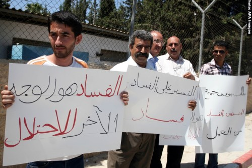 Palestinians take part in a protest outside the ministers council headquarters in the West Bank city of Ramallah on July 19, 2011, calling for the trial of ministers and officials accused of financial and administrative corruption . Photo by Issam Rimawi