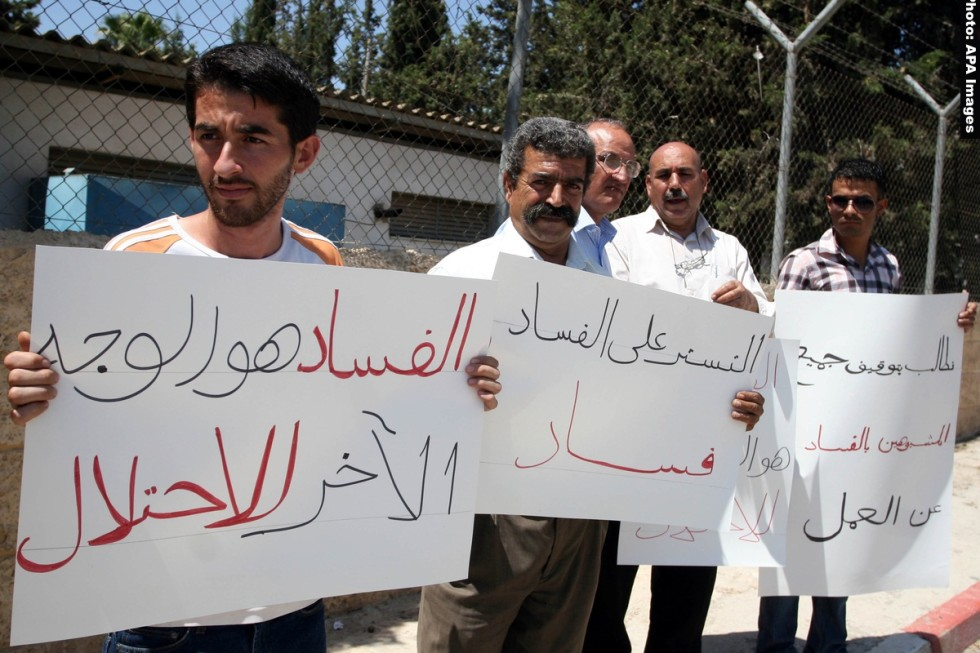 Palestinians take part in a protest outside the ministers council headquarters in the West Bank city of Ramallah