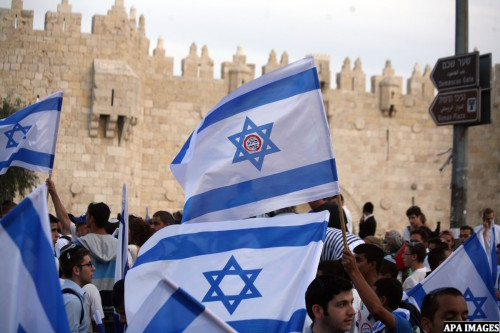 "Ultra-nationalist Israelis wave their national flags during the ""flag march"" through Damascus Gate in east Jerusalem on May 28, 2014 as the country celebrates the anniversary of its capture in the 1967 Six-Day War. Fearing clashes, police closed the flashpoint Al-Aqsa mosque compound to visitors and in Jerusalem Day speeches Prime Minister Benjamin Netanyahu pledged to never allow the city to be divided. Photo by Saeed Qaq"
