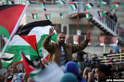 Palestinian prisoner Samer al-Issawi, who held a hunger strike for eight months, is greeted by people  during  celebrates his release from an Israeli jail in the East Jerusalem neighborhood of Issawiya,  December 28, 2013. Israel freed al-Issawi from jail after completing a deal agreed in exchange for him halting the hunger strike that almost killed him. His confinement had stoked weeks of protests in the Israeli-occupied West Bank. Israel convicted Issawi of shooting at an Israeli bus in 2002 but released him in 2011 along with more than 1,000 Palestinian prisoners. He was re-arrested in July 2012 after Israel said he violated the terms of his release by crossing from his native East Jerusalem to the West Bank. Photo by Saeed Qaq