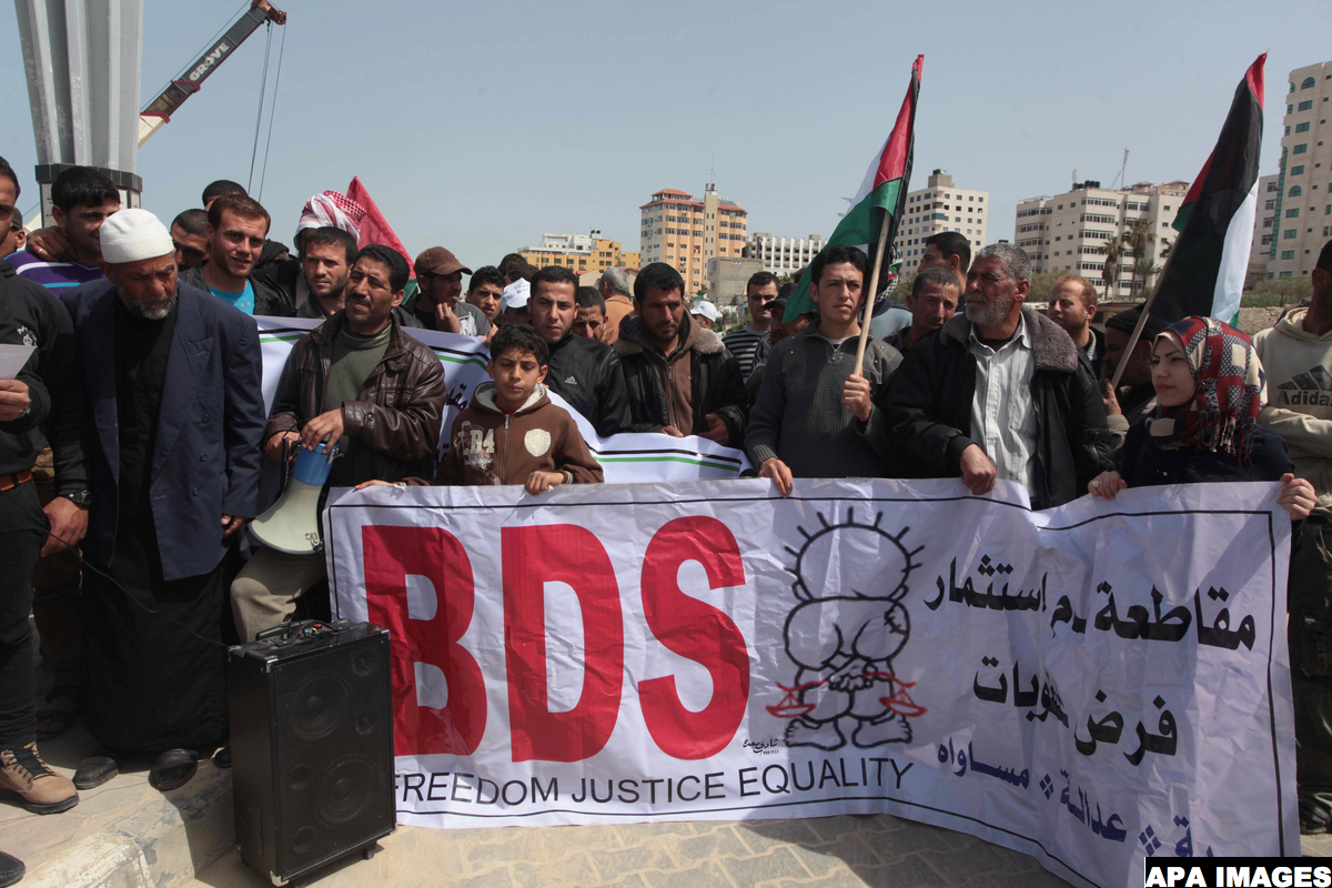 Palestinian fishermen hold banners in a protest to demand the boycott of the Israeli agricultural products, during the 10th annual Israeli Apartheid Week, at the seaport of Gaza City on March 16, 2014. Photo by Ashraf Amra