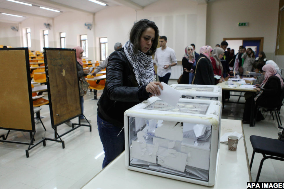 A Palestinian student of Birzeit University, casts her vote during the University students council elections, in the outskirts of the city of Ramallah in the West Bank on April 22, 2015. Photo by Shadi Hatem